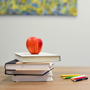 Apple placed on top of school books.